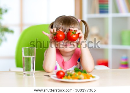 funny child little girl playing with vegetables - stock photo