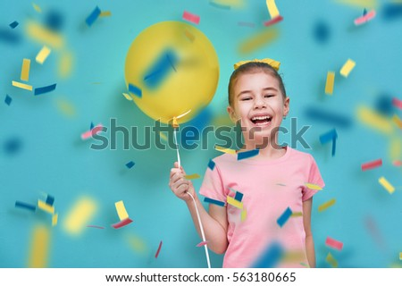 Funny child on a background of bright blue wall. Girl is having fun with balloons and confetti. Yellow, pink and turquoise colors.