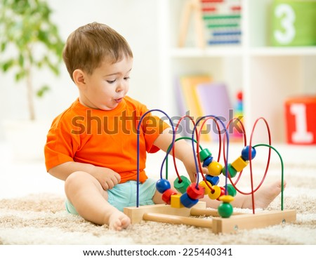 funny child playing with educational toy indoors - stock photo