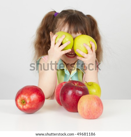 Funny child playing with two apples on table - stock photo