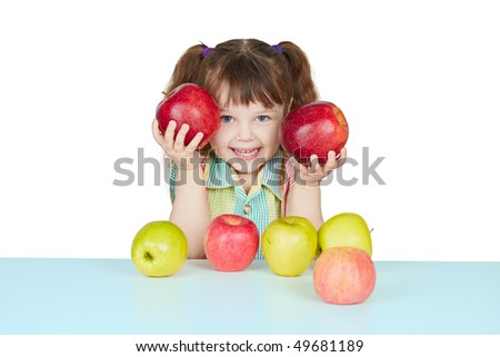 Funny child playing with two red apples on blue table - stock photo