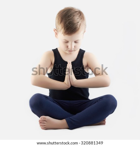 funny child practicing yoga isolated on white background. little Boy does yoga - stock photo