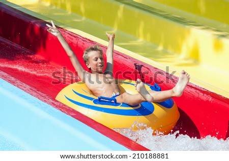 Funny child taking a fast water ride on a float splashing water. Summer vacation concept.  - stock photo