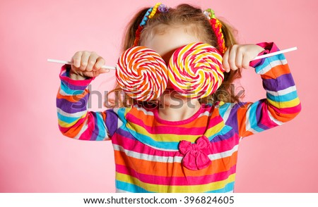 Funny child with candy lollipop, happy little girl eating big sugar lollipop, kid eat sweets. surprised child with candy. isolated on bright background, studio. Beautiful little girl with lollipop - stock photo