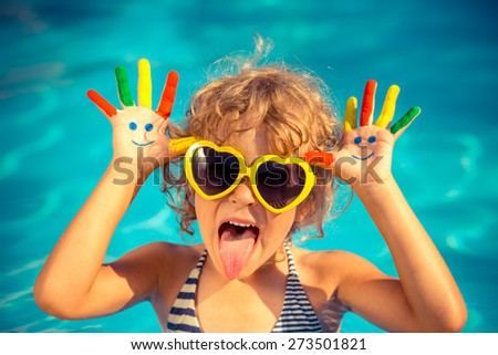Funny child with drawing smiley on hands in swimming pool. Summer vacation concept - stock photo