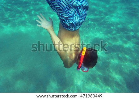 Funny child with snorkel mask and pipe diving in sea enjoying summer vacation.