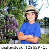Funny child with straw hat in the park with a lake - stock photo