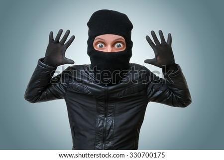 Funny childlike burglar or bandit puts hands up. - stock photo