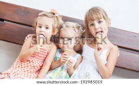 funny children girls eating ice cream sitting on a bench on a white background  - stock photo