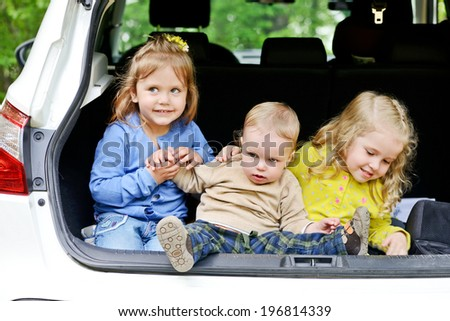 funny children sitting in the car - stock photo