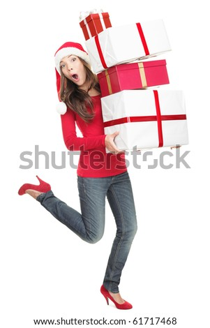 Funny Christmas Santa woman in hurry running with gifts looking surprised / shocked in Santa hat. Cutout full length portrait of multiracial Asian Chinese / white Caucasian young woman. - stock photo
