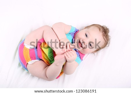 Funny chubby baby girl playing with her feet - stock photo