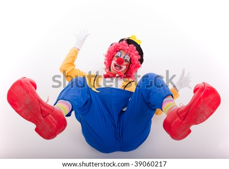 funny circus clown falling on the floor (isolated on white) - stock photo