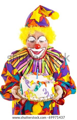 Funny clown blows out a candle on the birthday cake.  Isolated on white.