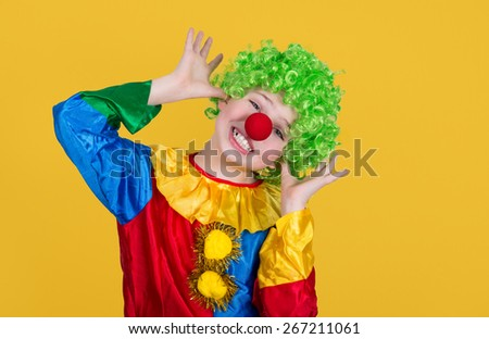 Funny clown isolated on yellow background. Closeup of little clown in green wig. - stock photo