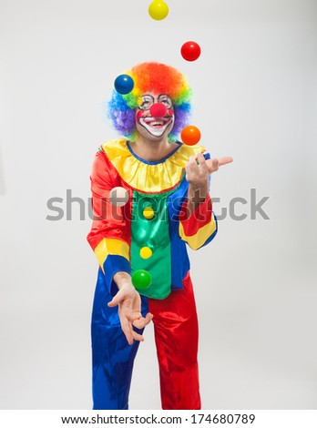Funny clown juggling balls - stock photo