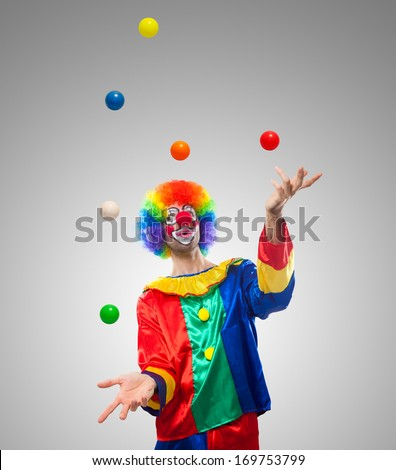Funny clown juggling many balls - stock photo