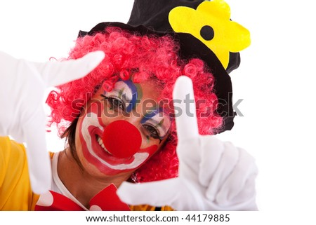 funny clown peeking between his fingers (hand framing) - stock photo