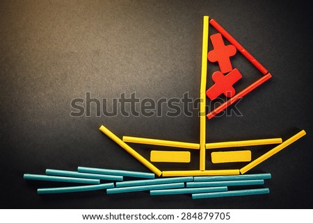 Funny composition presents lonely boat on sea, made of wooden sticks in various colors.  - stock photo