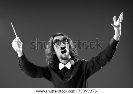 Funny conductor against dark background - stock photo