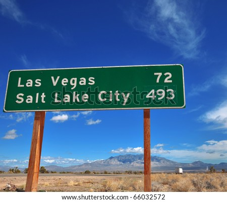 Funny contrast of cities on a road sign. - stock photo