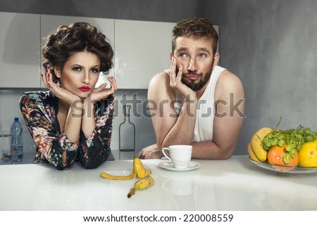 Funny couple after breakfast. Strange faces. Young man and beauty woman in kitchen - stock photo
