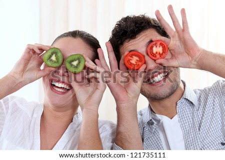 Funny couple covering their eyes with fruit - stock photo