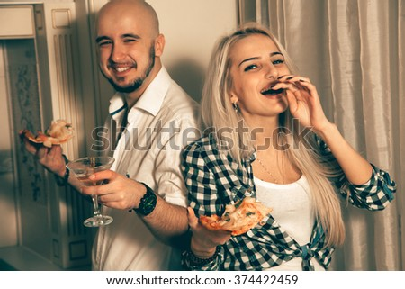 Funny couple laughing at a party with pizza. Celebrate, disco, party, nightlife, entertainment, friendship concept. - stock photo