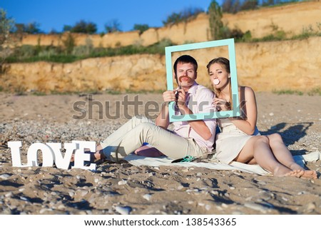 funny couple on the beach - stock photo