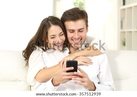 Funny couple or marriage sharing a smart phone to watch media content sitting on a couch at home - stock photo
