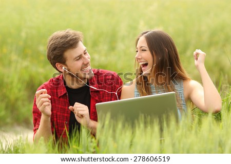 Funny couple singing and listening music from a laptop in a green field - stock photo