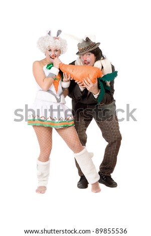 Funny couple with carrot dressed as rabbits. Isolated - stock photo