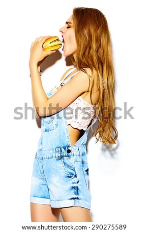 Funny crazy glamor stylish sexy smiling beautiful young blond woman model in summer bright hipster jeans cloth eating hamburger - stock photo
