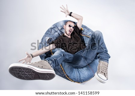 funny crazy man dressed in jeans and sneakers standing on denim beanbag - stock photo