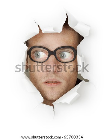 Funny crazy man face in old eyeglasses looking out of the hole isolated on white background - stock photo