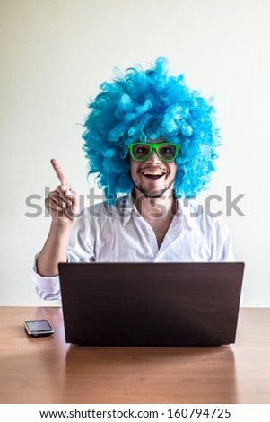 funny crazy young man with blue wig using notebook on the table - stock photo