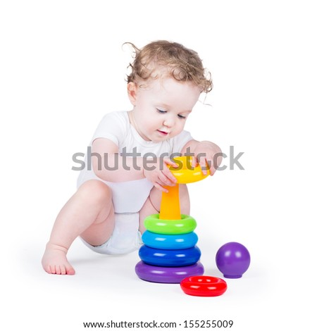 Funny curly baby girl playing with a colorful pyramid on white background - stock photo