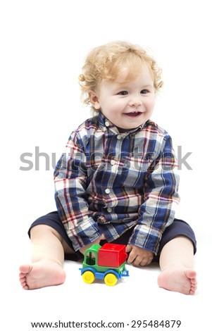Funny curly smiling baby boy playing with colored toy car isolated on white background, vertical photo