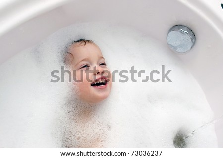 funny cute baby is swimming  in bath - stock photo
