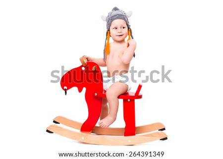 Funny cute baby sitting on the toy horse or elk in Asterix hat, smiling isolated on white - stock photo