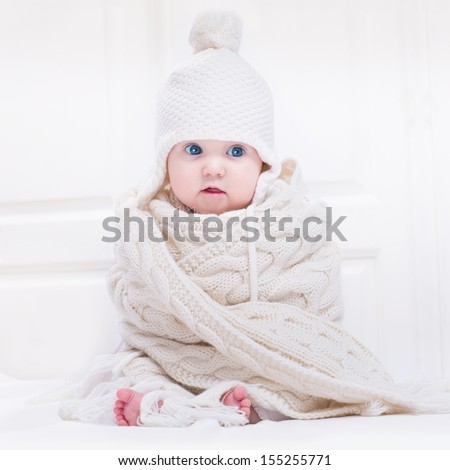 Funny cute baby with big blue eyes wearing a hat and a huge knitted scarf - stock photo