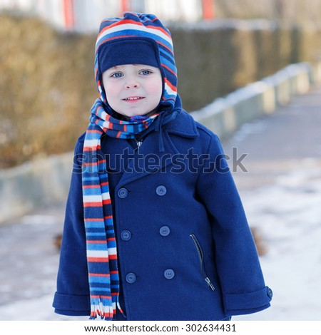 Funny cute boy smiling on beautiful winter snowy day. Kid boy in warm clothes with cap and coat, outdoors. Child freezing - stock photo