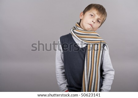 funny cute caucasian blond boy making grimace with colorful scarf standing isolated over gray background