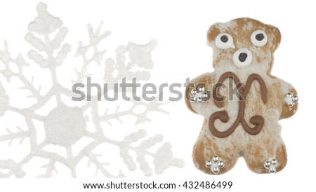 funny cute delicious gingerbread bear, decorated with a pattern and a silver sugar balls and snowflakes on a white background isolated - stock photo