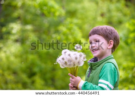 Funny cute kid boy having fun with dandelion flower on warm and sunny summer day. Kid blowing on flower, active outdoors leisure with children - stock photo
