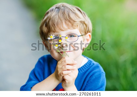 Funny cute kid boy with glasses walking happily in field on warm and sunny summer day. Kid having fun, active outdoors leisure with children - stock photo