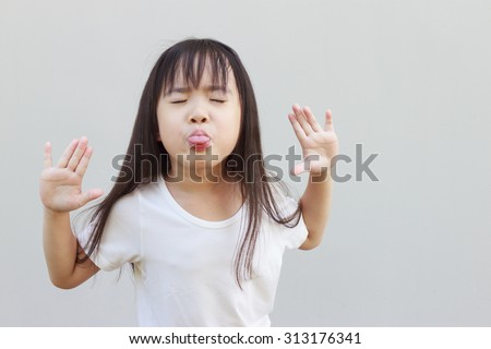 funny cute little asian girl shows the tongue - stock photo