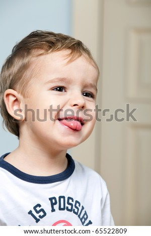 Funny cute little boy showing a tongue indoors