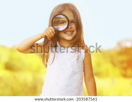 Funny cute little girl looking through a magnifying glass - stock photo