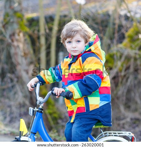 Funny cute  preschool kid boy in colorful raincoat riding his first bike and having fun on warm  day, outdoors. Active leisure with children in winter, spring or autumn. - stock photo